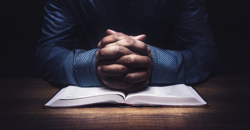 hands folded over bible in repentance, metanoia