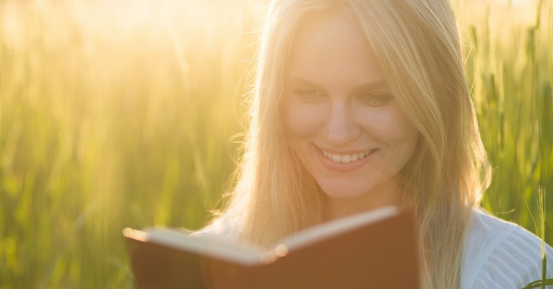 happy woman reading Bible outside in nature with sun shining, motivating Bible verses