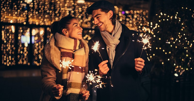 happy couple holding sparklers for New Year's bundled up for winter, marriage goals