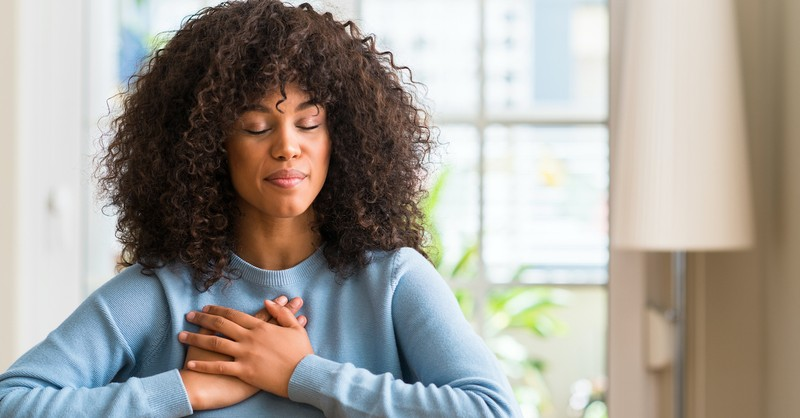 woman with closed eyes and prayer hands over chest sitting by windown
