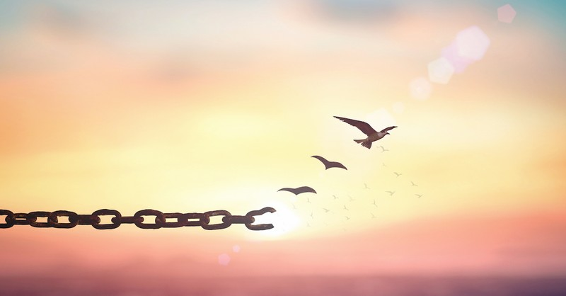 broken chains with birds flying off in sunset background to freedom, generational curses