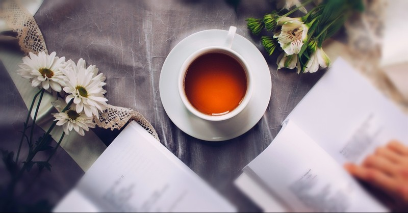 Poems, tea, and flowers on a blanket