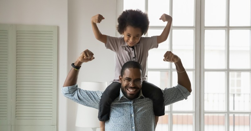 father and son flexing arm muscles being strong