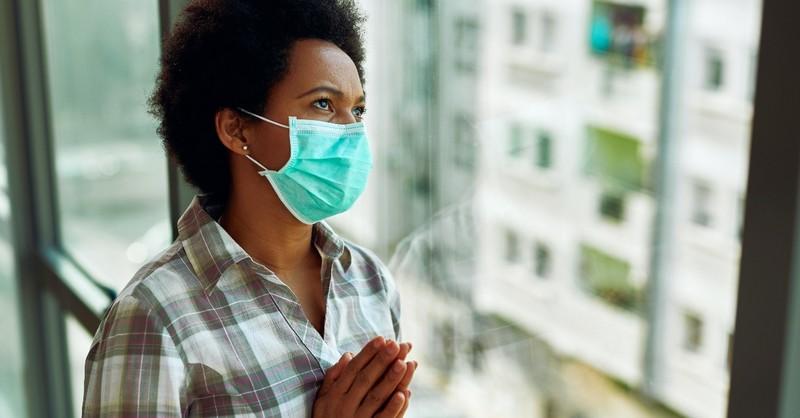 Woman in mask praying