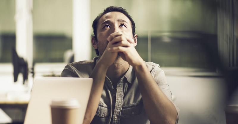 man looking upward with prayer hands at desk, God hears our prayers