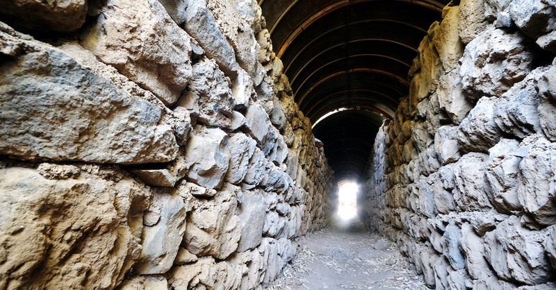 stone wall leading to narrow opening with bright light, narrow is the gate