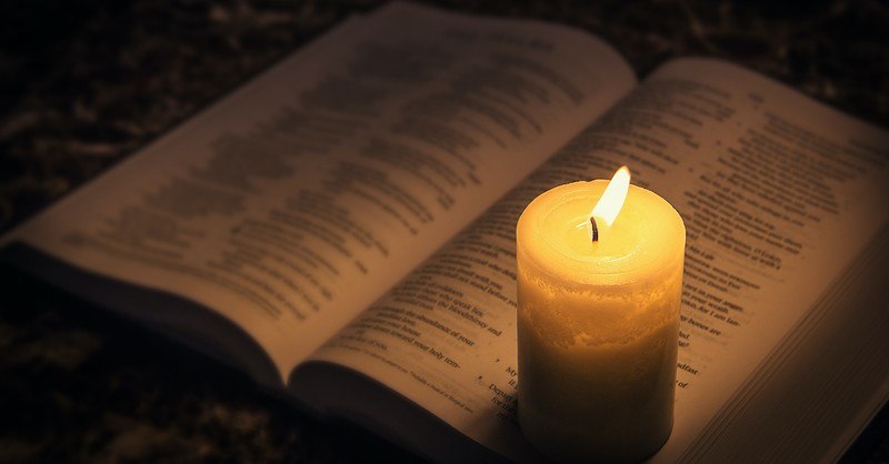 open Bible illuminated by candle sitting on Bible, God's Word is a lamp unto my feet