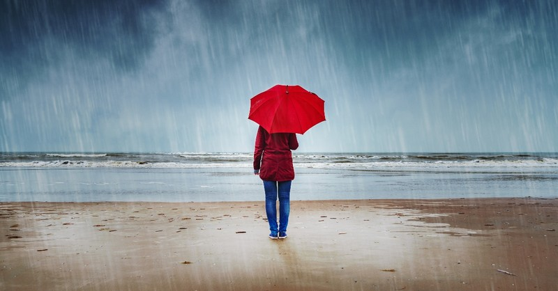 woman standing with umbrella in rain on beach, myths in church about mental health
