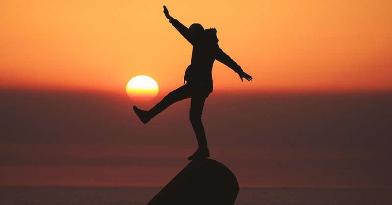 silhouette of person standing in front of setting sun looking excited