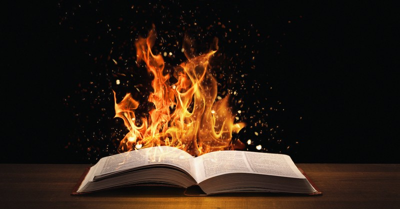 open Bible on table with flames rising behind it, seven deadly sins