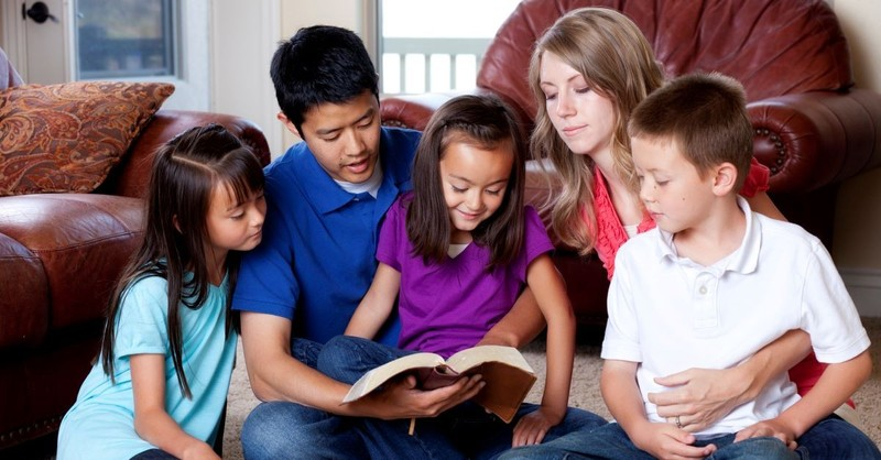 family sitting together reading bible