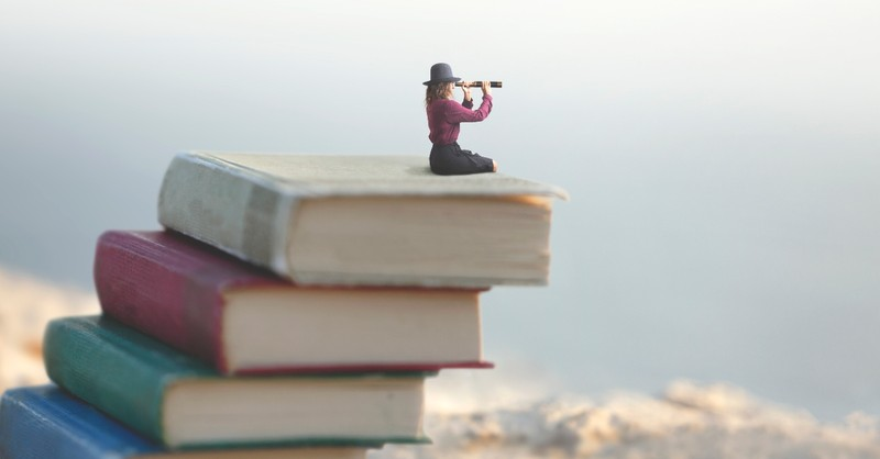 Woman looking out with a spy glass sitting on a pile of books