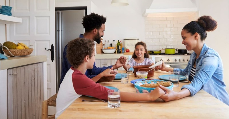 family praying around dinner table with kids