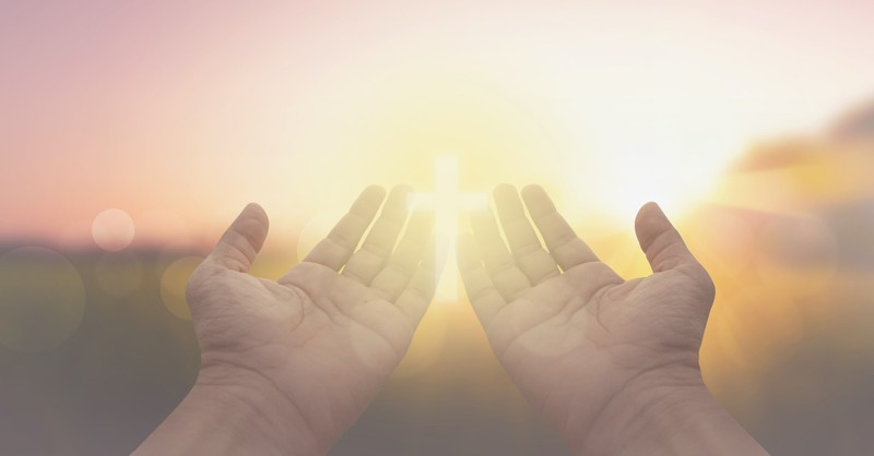 open prayer hands with concept of cross in bright light outside, Lord hear our prayer meaning