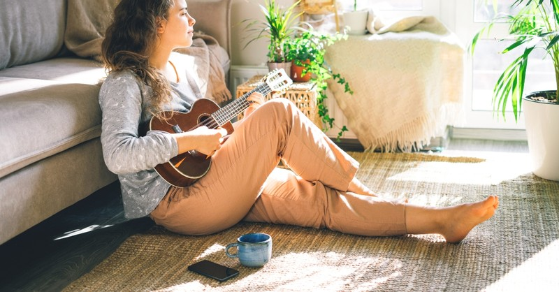 young woman playing music instrument at home alone