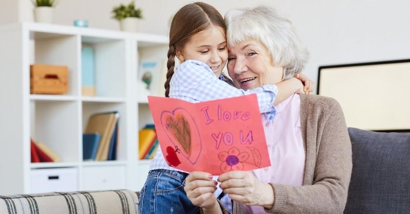 granddaughter hugging her grandmother giving her a valentines card