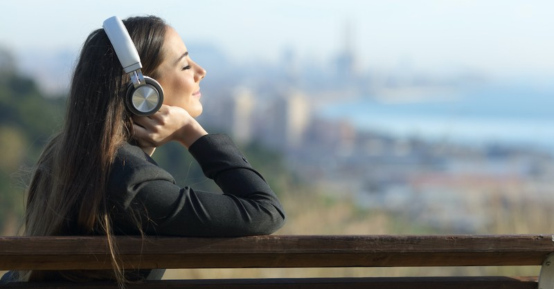 woman listing to headphones, faith comes by hearing