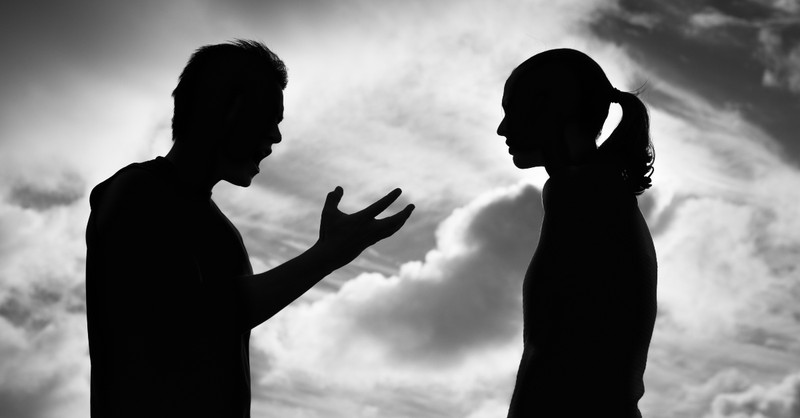 man and woman silhouette having argument, common roots of jealousy in marriage