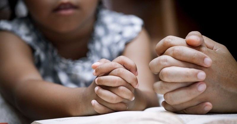 child and adult praying over bible together