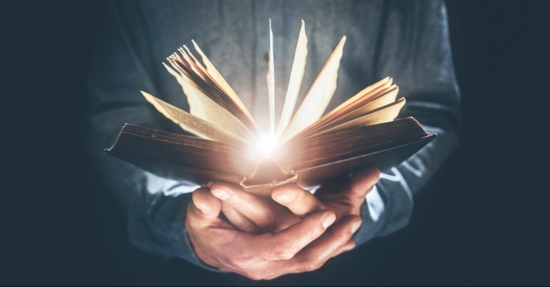 Bible glowing in a man's hands