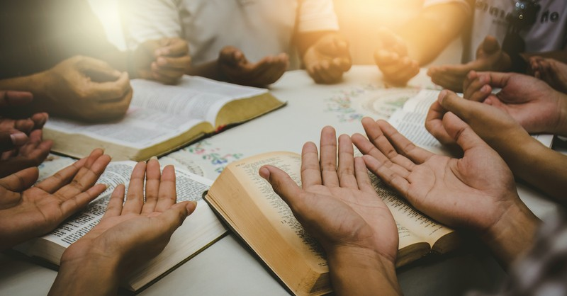 hands held over bibles, prayer for missionaries