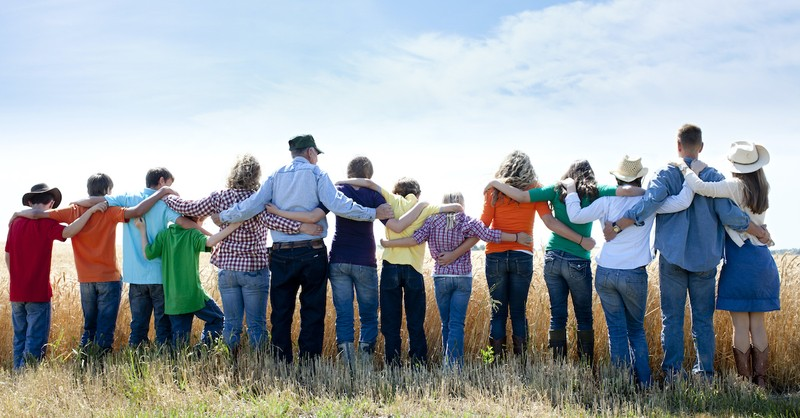 Group of people standing in a field, why do we stand for worship