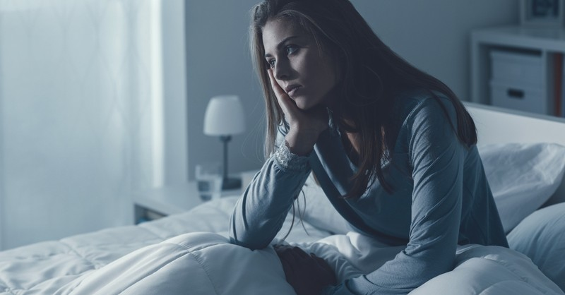 woman sitting up in bed looking anxious can't sleep, psalms for when you can't sleep