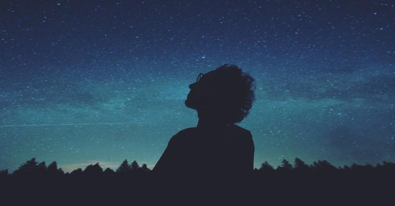 man looking up at night sky stars