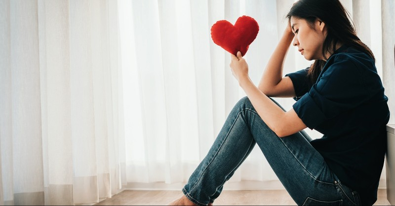 Troubled woman holding a plush heart