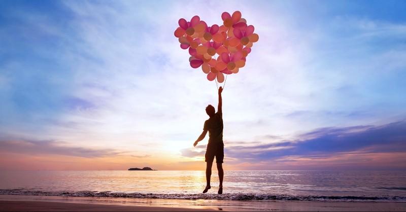 Man on the beach holding heart balloons