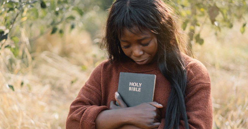 woman holding Bible outside in nature with head bowed in prayer, what is faith in Hebrews 11