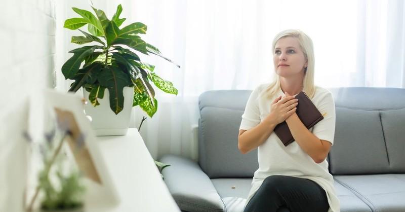 woman holding bible praying looking up praying clutching