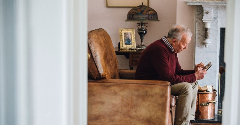 An elderly man looking sadly at a picture frame