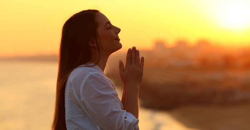 Woman praying outside under sunset, prayer for health