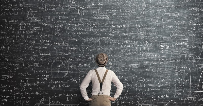 Man looking at a chalkboard of equations and diagrams
