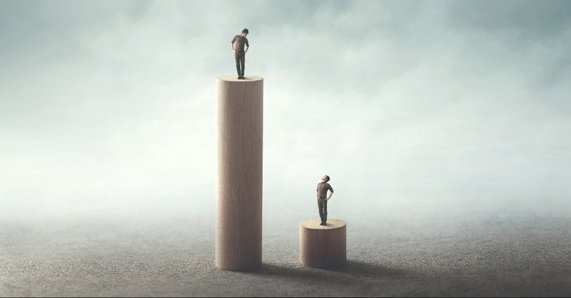 Two men on pedestals, one higher