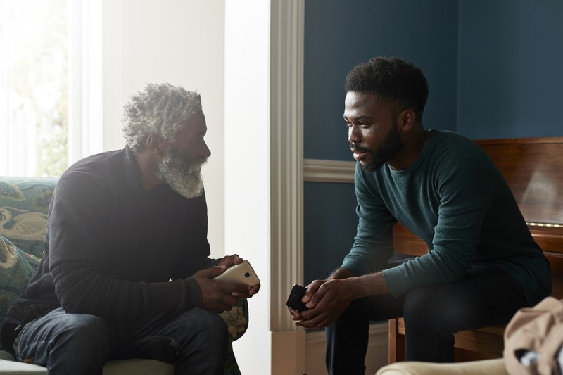 older father and son sitting in living room talking, honor your father and mother meaning