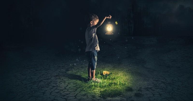 Boy holding a lantern in the dark