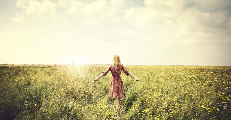 woman walking in a field, walk by faith not by sight