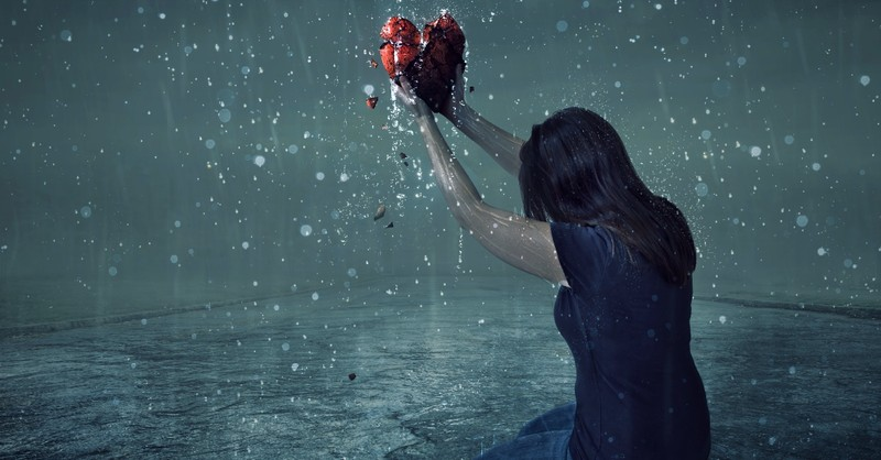 Woman holding a broken heart on her knees in the rain