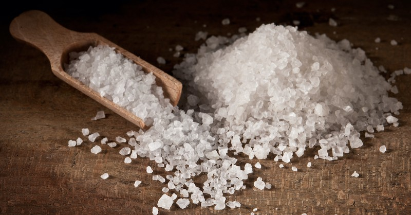 coarse grain salt on wooden table with wooden spoon, salt of the earth