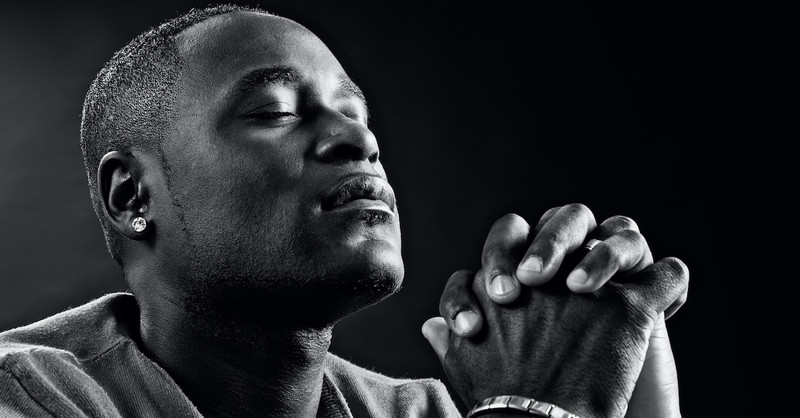 young black man praying with eyes closed and hands folded, how to trust in the Lord with all your heart