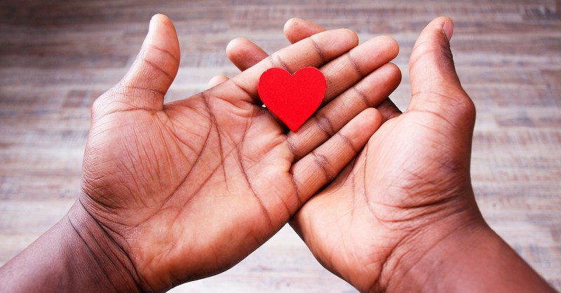 open hands holding paper red heart, guard your heart