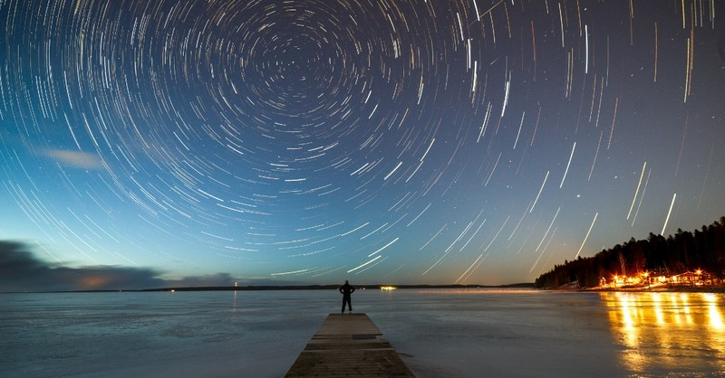 Time-elapse shot of evening stars turning in the sky over a body of water