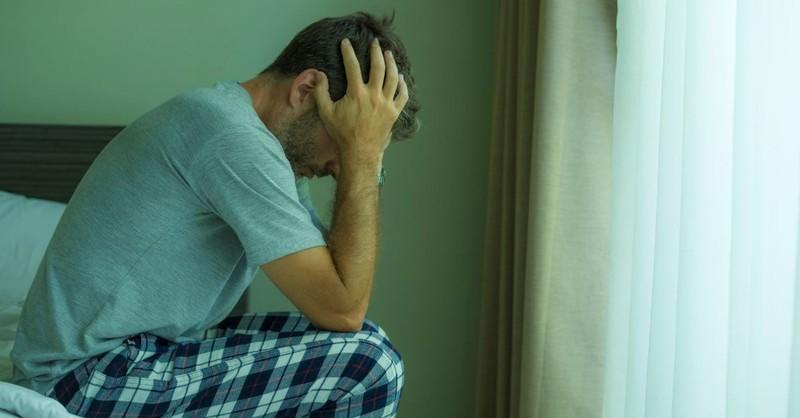 man head in hands depressed sad tired