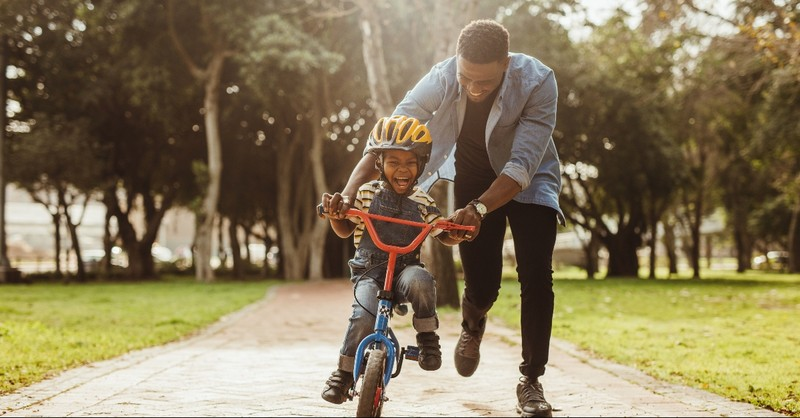 A father helping his son ride a bike