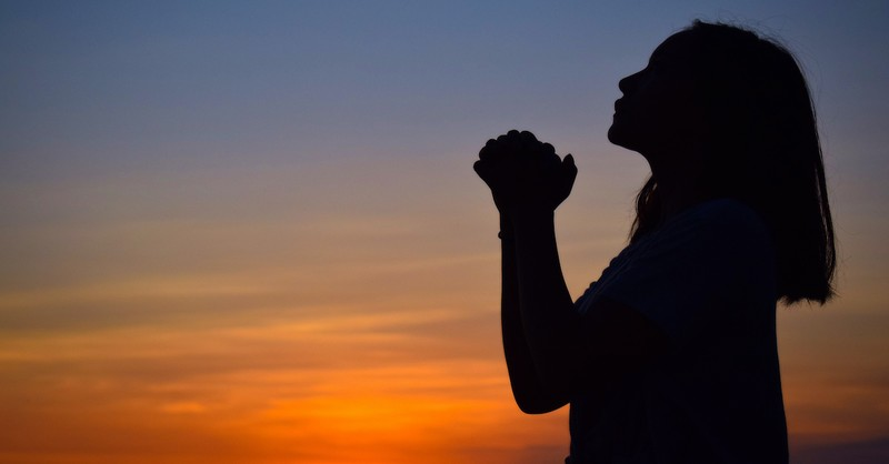 silhouette of woman praying at sunset, if God is for us who can be against us?