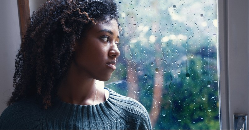 Woman looking out a rainy window, many are the afflictions of the righteous