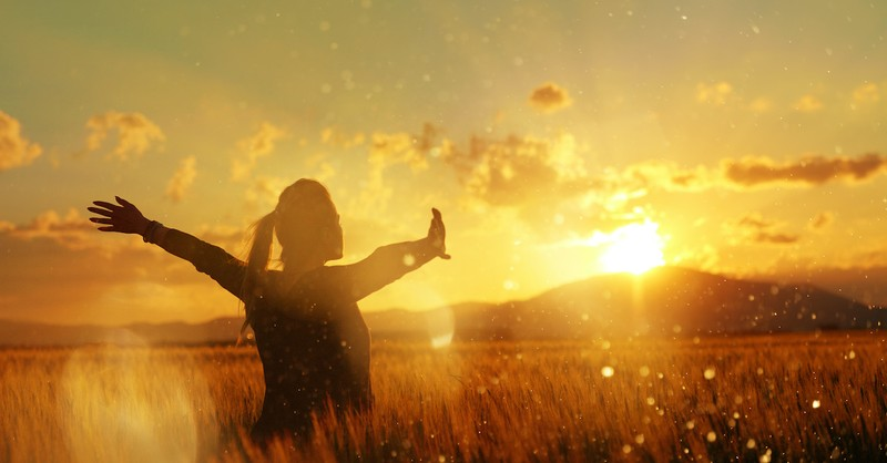 silhouette of woman praising in a field at sunset, grow in grace