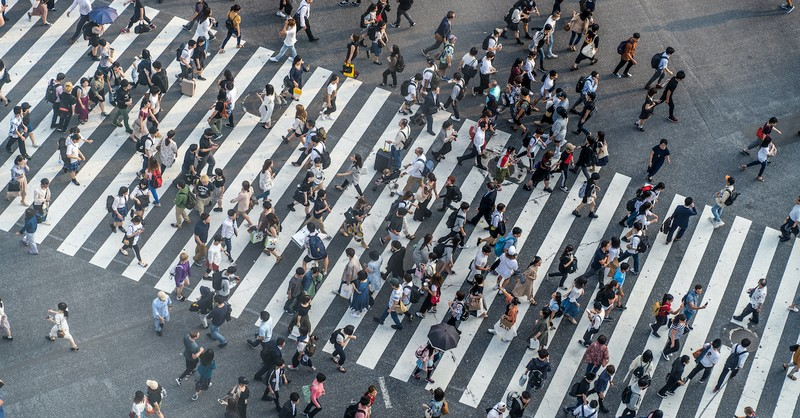 crowded crosswalk filled with people walking, how does bad company corrupt